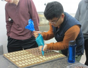 JMU student attempts to make the signature Antwerp Chocolate Hand at a local chocolatier.